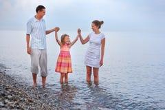 Caminata feliz de la familia en la playa, ensamblando las manos Fotografía de archivo