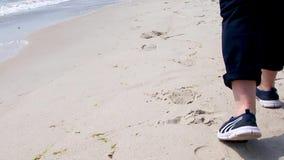 Caminata a lo largo del mar Las piernas femeninas van a lo largo de la playa a lo largo del oc?ano, primer almacen de video