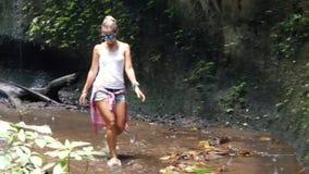 Camine a la cascada a lo largo de la trayectoria en la selva tropical Bali, almacen de metraje de vídeo