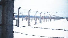 Camine a lo largo de la cerca vieja del alambre de púas del campo nazi de la concentración y de la exterminación en la nieve víde almacen de metraje de vídeo