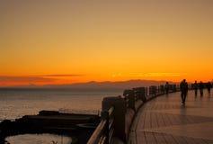 Camine por el mar con la silueta de la gente en la puesta del sol fotografía de archivo libre de regalías