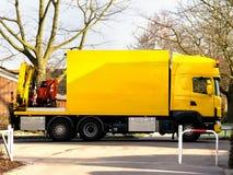 Caminhão amarelo com a mini máquina escavadora urbana Fotografia de Stock