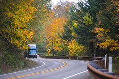 Caminhão azul na estrada espetacular do autemn do enrolamento Fotografia de Stock Royalty Free