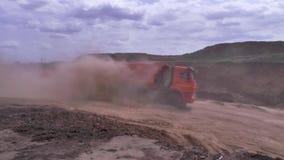 Caminhão basculante na estrada de terra na grande nuvem de poeira cena Névoa da poeira na estrada da pedreira após o caminhão de  filme