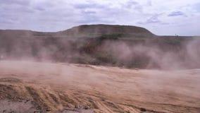 Caminhão basculante na estrada de terra na grande nuvem de poeira cena Névoa da poeira na estrada da pedreira após o caminhão de  vídeos de arquivo