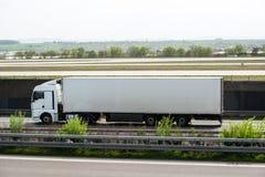 Caminhão branco que move sobre uma estrada Foto de Stock Royalty Free