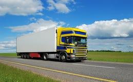Caminhão com a cabine azul-amarela que move sobre a estrada. Fotografia de Stock Royalty Free