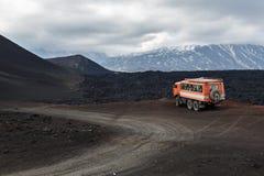 Caminhão da expedição na estrada da montanha perto dos campos e dos vulcões de lava Fotos de Stock