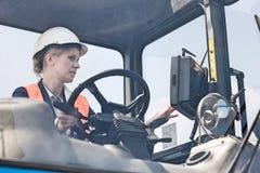 Caminhão de empilhadeira de funcionamento do trabalhador fêmea na jarda de envio imagens de stock