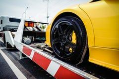 Caminhão de reboque da cama lisa que carrega um veículo quebrado imagens de stock royalty free