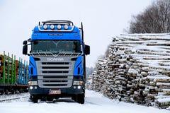 Caminhão de registro azul de Scania V8 na jarda Railway nevado da madeira Imagem de Stock