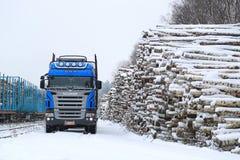 Caminhão de registro azul de Scania V8 na jarda Railway nevado da madeira Fotos de Stock