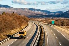 Caminhão de serviço público amarelo na estrada do país imagem de stock