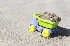 Caminhão do brinquedo das crianças com areia Conceito do transporte dos bens e dos materiais de constru??o imagem de stock royalty free