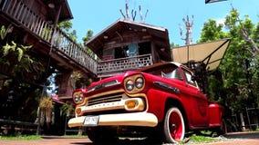 Caminhão do luz-dever de Chevrolet com casas de madeira ao redor filme