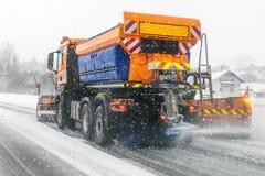 Caminhão do Snowplow que remove a neve suja da rua ou da estrada da cidade durante quedas de neve pesadas Situação da estrada do  imagem de stock