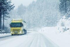 Caminhão do tráfego na estrada do inverno no blizzard da neve imagens de stock
