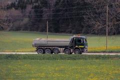 Caminhão grande que conduz em uma estrada nas madeiras Imagens de Stock Royalty Free