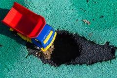 Caminhão plástico do brinquedo com um corpo vermelho parado na frente do poço O carro não pode ir Furo no asfalto A estrada p fotografia de stock