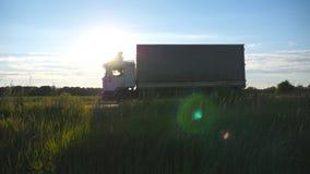 Caminhão que conduz em uma estrada com o alargamento do sol no fundo O caminhão monta através do campo com paisagem bonita filme
