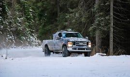 caminhão 4x4 que deriva na estrada da neve do inverno na floresta Imagens de Stock
