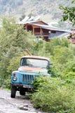 Caminhão soviético oxidado azul agrícola velho em madeiras verdes perto da estrada na aldeia da montanha, Mestia, Svaneti, Geórgi fotos de stock
