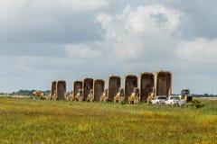 Caminhões basculantes alinhados em um pasto verde Foto de Stock
