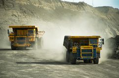 Caminhões basculantes em uma mina de carvão em um dia ensolarado imagens de stock