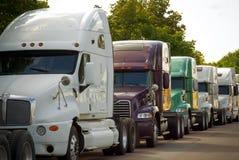 Caminhões comerciais grandes do transporte alinhados na estrada Imagem de Stock