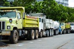 Caminhões da construção, algum amarelo, algum branco, estacionado em uma linha u Fotografia de Stock