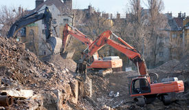 Caminhões da demolição na ação. Demolição de um bloco de planos velho. Fotografia de Stock
