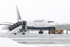 Caminhões da ponte e do aeroporto do embarque do passageiro perto de Boeing 767 no aeroporto Petropavlovsk-Kamchatsky Foto de Stock Royalty Free