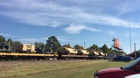 Caminhões de exército dos EUA na estrada de ferro que está sendo transportada pelo trilho video estoque