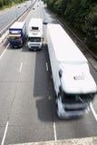 Caminhões de lado a lado na estrada Imagem de Stock