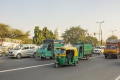 Caminhões e riquexós verdes indianos do moto no tráfego de cidade em um fundo de árvores verdes e na abóbada da foto de stock