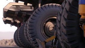 Caminhões eretos de uma roda enorme dump truck Caminhões pesados enormes de estacionamento Caminhão de mineração Os caminhões bas filme