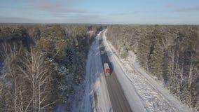 Caminhões que conduzem ao longo da estrada do inverno com opinião aérea das árvores cobertos de neve video estoque