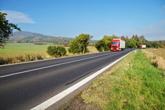 Caminhões vermelhos na estrada no campo Fotos de Stock Royalty Free