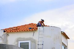 Caminha, Moledo, Viana do Castelo, Spain. A construction worker is finishing the roof of a new holiday home in the evening sun Royalty Free Stock Photos
