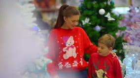A caminhada alegre ao longo do shopping da mãe e de seu filho em ligações em ponte do Natal video estoque
