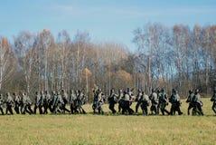 Caminhada alemão dos soldados-reenactors com armas Fotografia de Stock Royalty Free