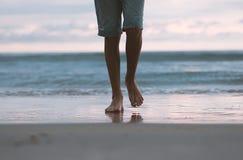 A caminhada ao longo da ressaca do mar, pés na ressaca, Imagem de Stock