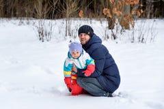 Caminhada da família na mamã e na criança do paizinho da floresta do inverno foto de stock royalty free