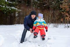Caminhada da família na mamã e na criança do paizinho da floresta do inverno imagem de stock royalty free