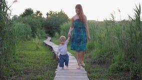 A caminhada da família na natureza, mãe feliz nova conduz a mão de pouco filho ao andar na ponte de madeira fora entre a grama video estoque