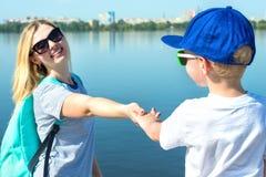 Caminhada da mãe e do filho ao longo do passeio e para guardar as mãos imagens de stock