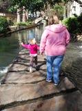 Caminhada da matriz e da criança ao longo do Riverwalk imagem de stock