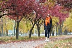 Caminhada da menina do ruivo no caminho no parque da cidade, outono Fotos de Stock Royalty Free