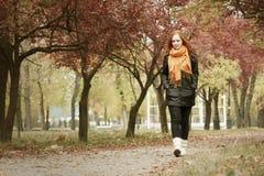 Caminhada da menina do ruivo no caminho no parque da cidade, outono Imagens de Stock