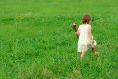 Caminhada da menina no campo verde Imagens de Stock